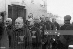 Homosexual prisoners at the concentration camp at Sachsenhausen, Germany, wearing pink triangles on their uniforms, are marched outdoors by Nazi guards on December 19, 1938. | Location: Sachsenhausen, Germany. (Photo by ? CORBIS/Corbis via Getty Images)