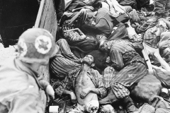 A U.S. 7th Army medical corpsman, newly arrived with liberating troops, looks into a train car piled with the emaciated and mutilated corpses of men from the Dachau-Birkenau concentration camps. (Photo by ? CORBIS/Corbis via Getty Images)
